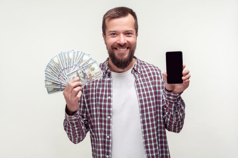 Online payment, mobile banking. Portrait of joyous bearded man holding smartphone and lot of money. white background stock photography
