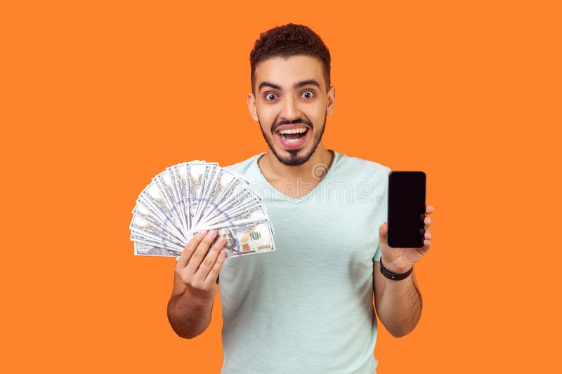 Online payment. Portrait of extremely happy man holding money and cellphone. indoor studio shot isolated on orange background stock images