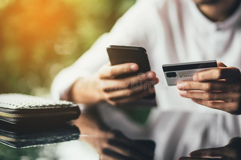 Online payment and shopping concept. male holding cell phone in one hand and credit card in other, making transaction stock photos