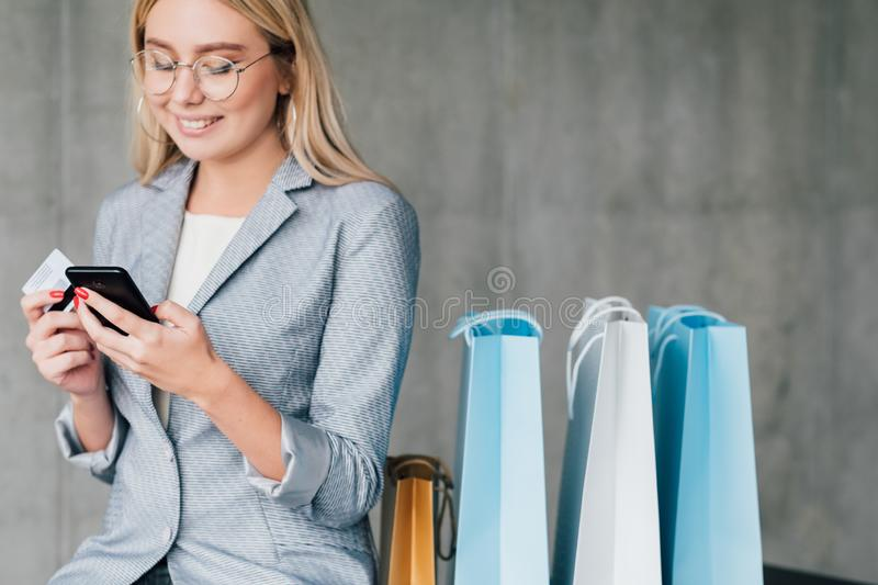 Online payment credit card smartphone copy space. Online payment. Smiling young woman with credit card shopping via smartphone. Copy space on grey background stock photo