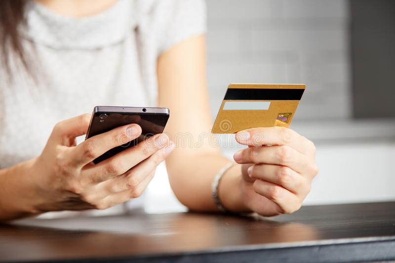Online payment, women`s hands holding a credit card and using smart phone for online shopping.  stock photos