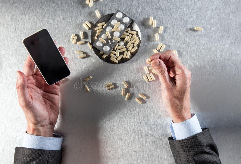 Online pharmacy concept - businessman hands holding phone to order drugs. Online pharmacy concept - businessman hands holding a cell phone to order drugs or royalty free stock image