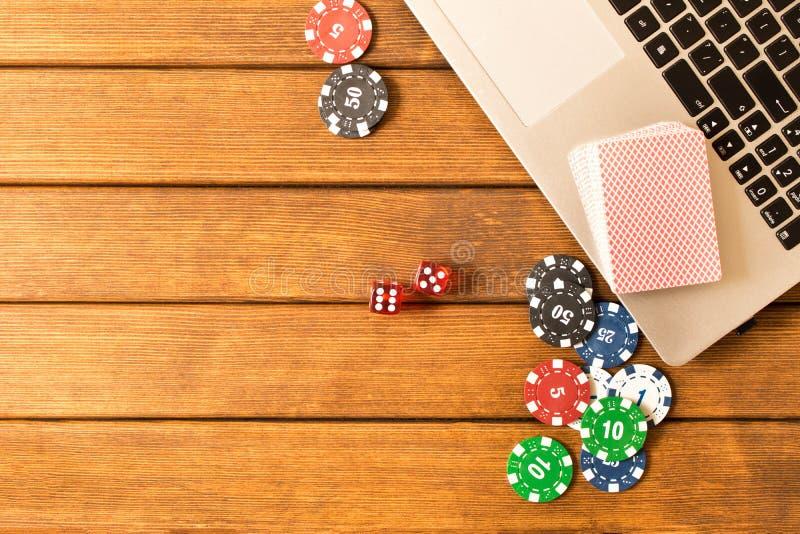 Online-poker Bärbar dator pokerchiper, tärning, en kortlek på en wo royaltyfri foto