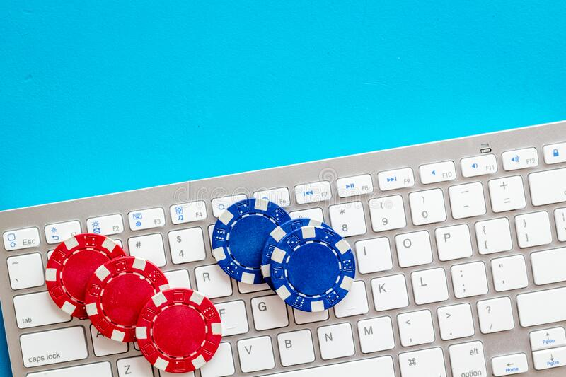 Online poker. Chips near keyboard on blue background top-down copy space royalty free stock photos