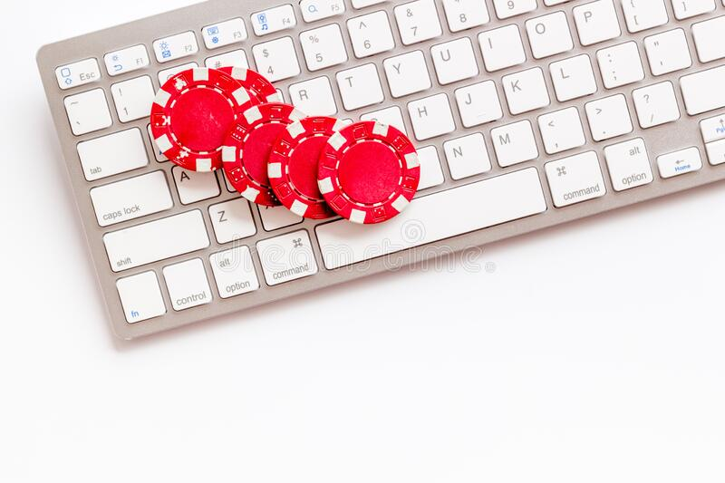 Online poker. Chips near keyboard on white background top-down copy space royalty free stock photography