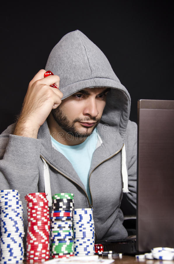 Online poker player. Isolated on black, thinking next move stock image