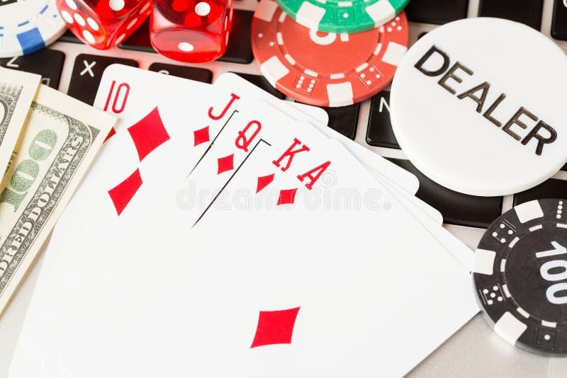 Online pokercasinothema Gambling chips met dok, speelkaarten, Amerikaanse dollars en dealerchips op laptop stock afbeelding