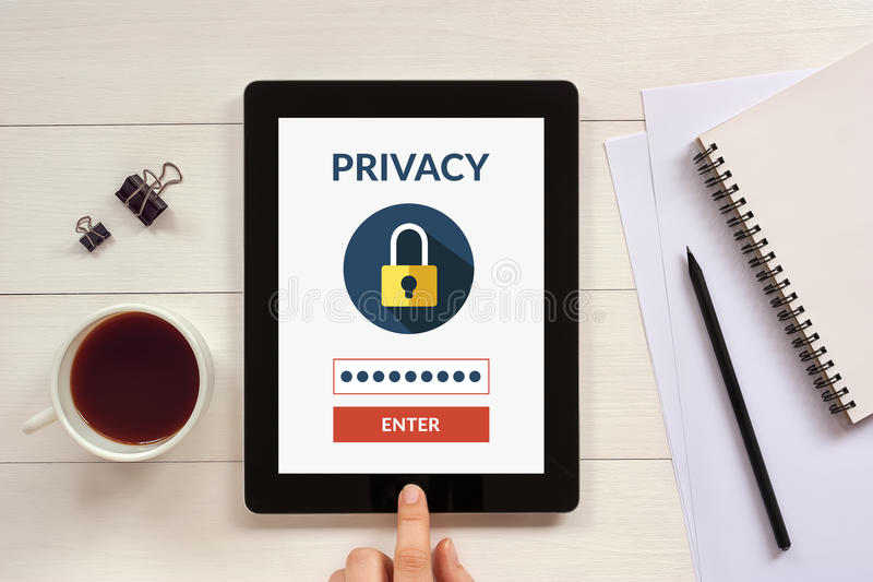 Online privacy concept on tablet screen with office objects. On white wooden table. All screen content is designed by me stock photography