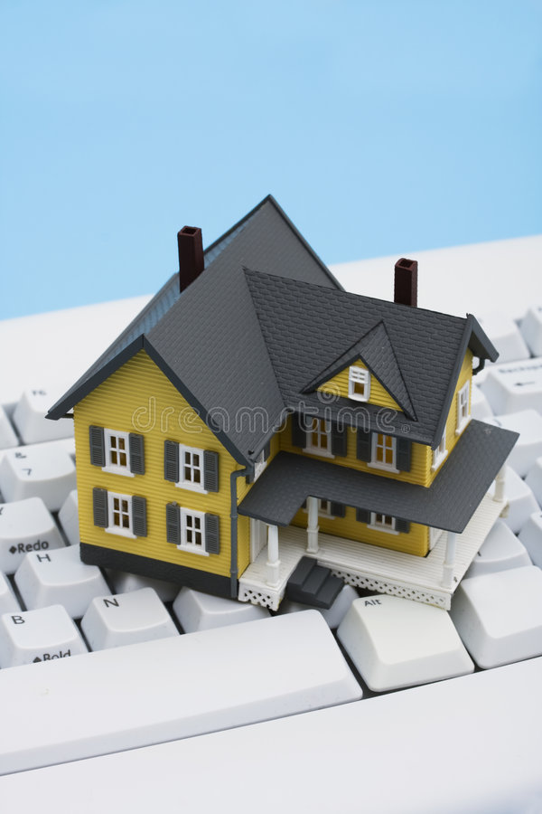 Online Real Estate. Model house sitting on a white keyboard stock images