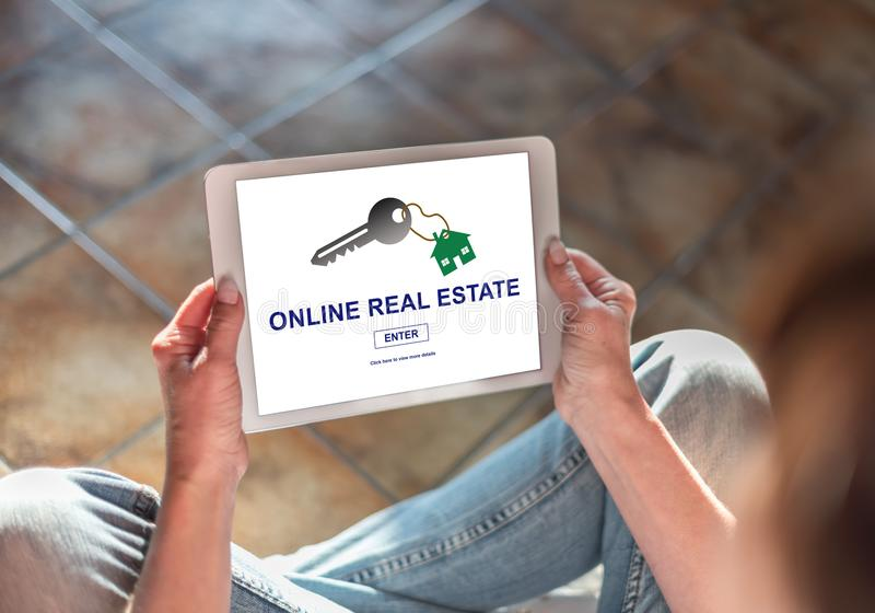 Online real estate concept on a tablet. Woman sitting on the floor with a tablet showing online real estate concept royalty free stock photography