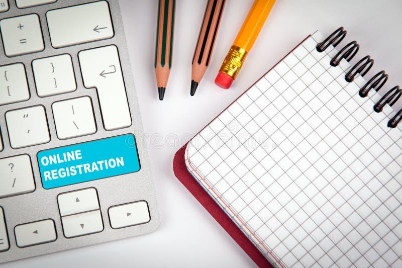 Online rejestraci pojęcie Komputerowa klawiatura na białym biurowym biurku z różnorodnymi rzeczami obrazy stock