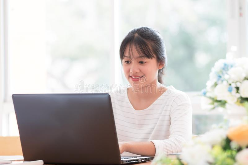 Online searching social networks by Smartphone Concept: Asian Cute Woman using black laptop computer for shopping or typing sms royalty free stock image
