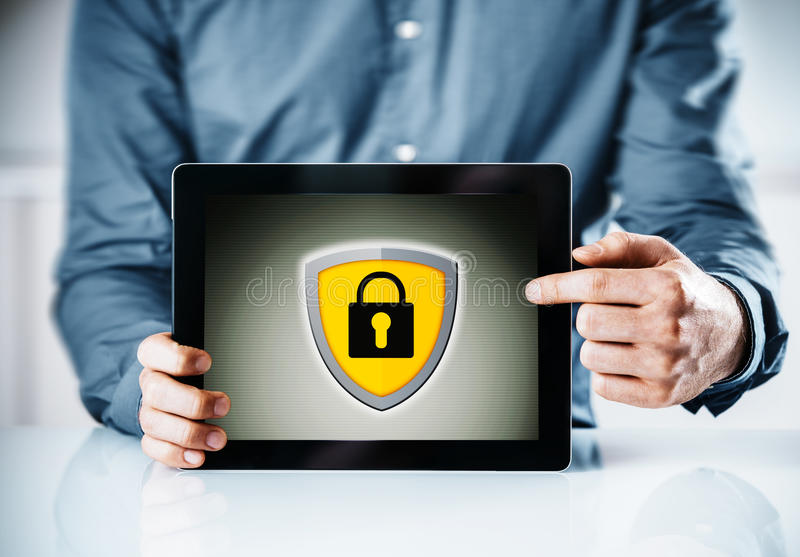 Online security concept. With a man holding a tablet computer pointing to the screen displaying a yellow shield and padlock icon stock photos