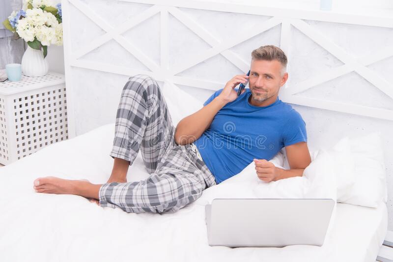 Online services. Remote work concept. Social networks. Online world. Man surfing internet work online. Digital marketing. Remote access. Mature man pajamas royalty free stock photography