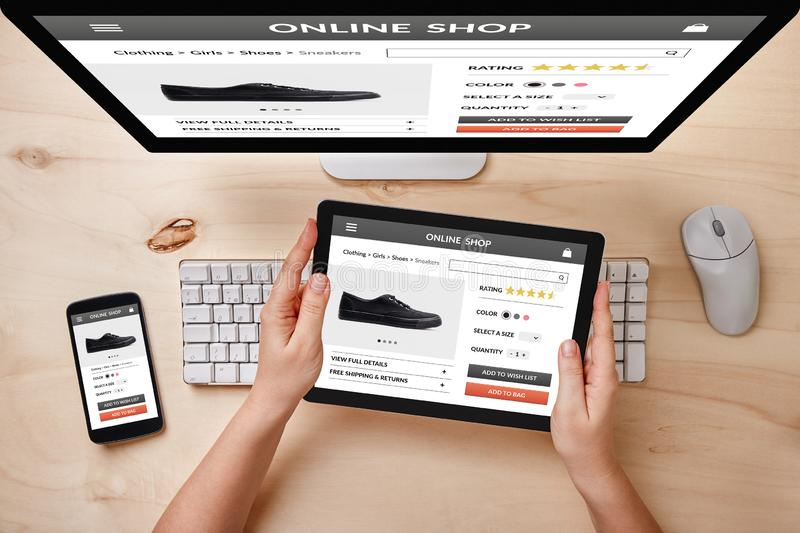 Online shop concept on responsive devices. Online shop concept on computer, tablet and smartphone screen over wooden table. Top view of responsive devices royalty free stock images