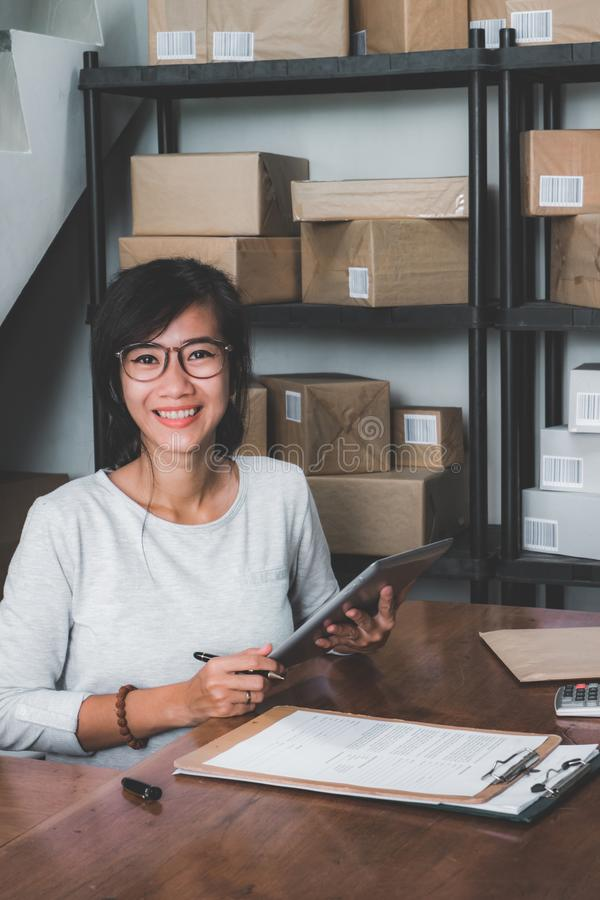 Online shop seller working at home office. Smiling young asian woman in package shelf. online shop seller at home office royalty free stock images