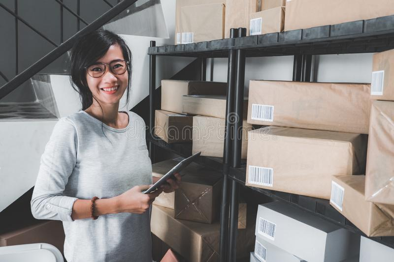 Online shop seller working at home office. Smiling young asian woman in package shelf. online shop seller at home office stock image