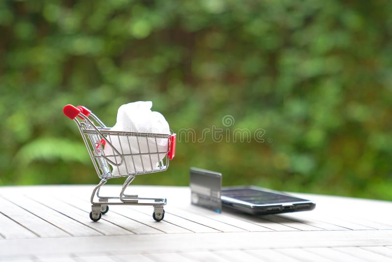 Online-shoppa begrepp: spårvagnvagn och en smart telefon arkivbilder
