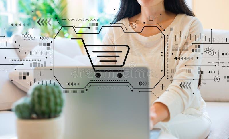 Online-shoppa tema med kvinnan som anv?nder hennes b?rbar dator royaltyfri foto