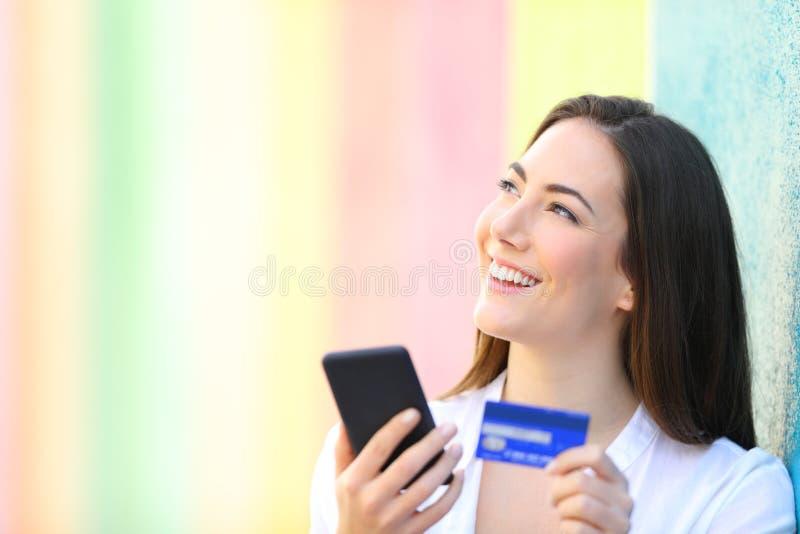 Online-shoppare som tänker rymma telefonen och kreditkorten royaltyfri foto