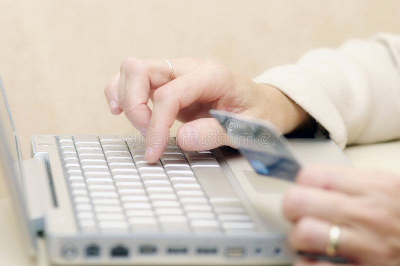 Online shopping. Woman using a credit card to buy goods online
