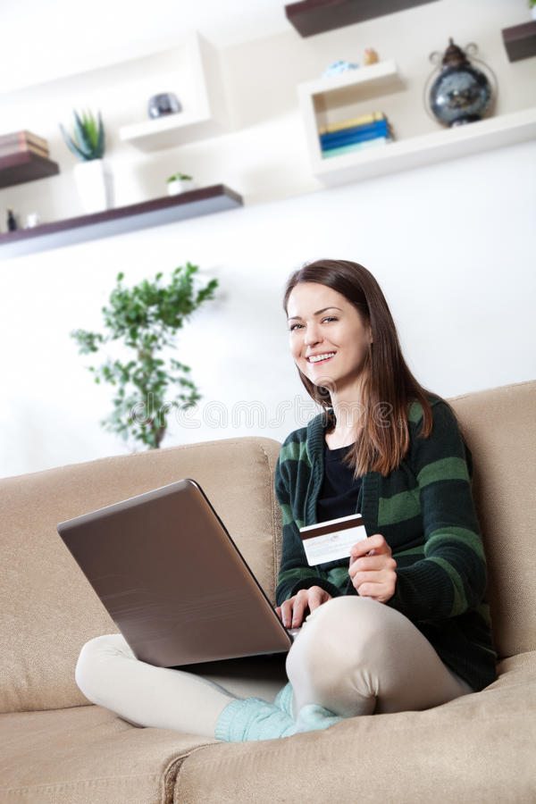 Online shopping. Happy young woman using her credit card for online shopping royalty free stock photo