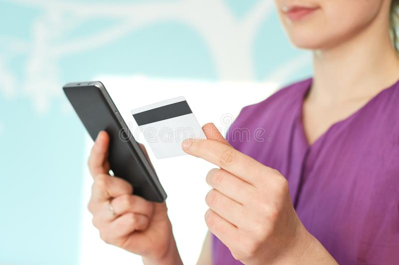 Online shopping concept. Close up of unrecognizable female model holds modern mobile phone and credit card, surfes internet websto royalty free stock image