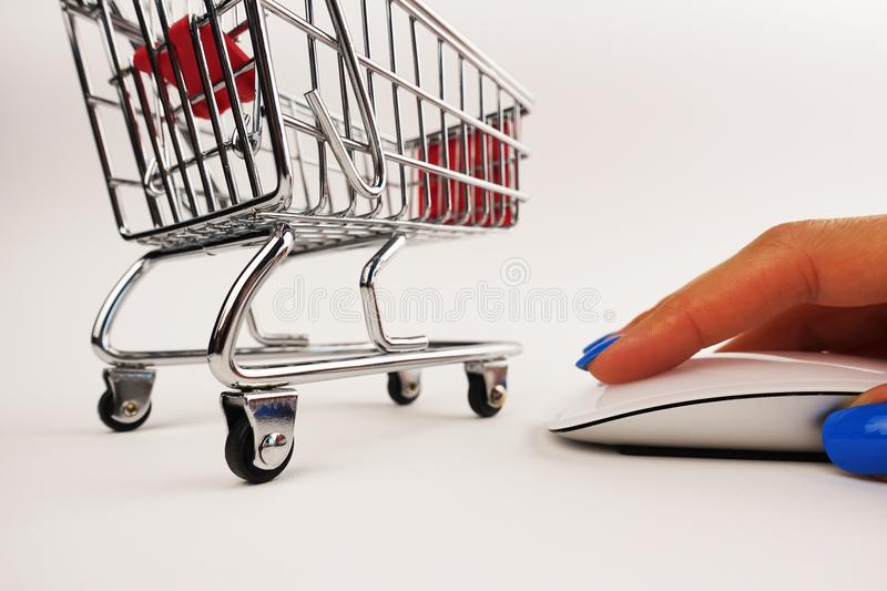 Online shopping concept with mini shopping car in front of computer mouse controlled by young woman hand stock photography