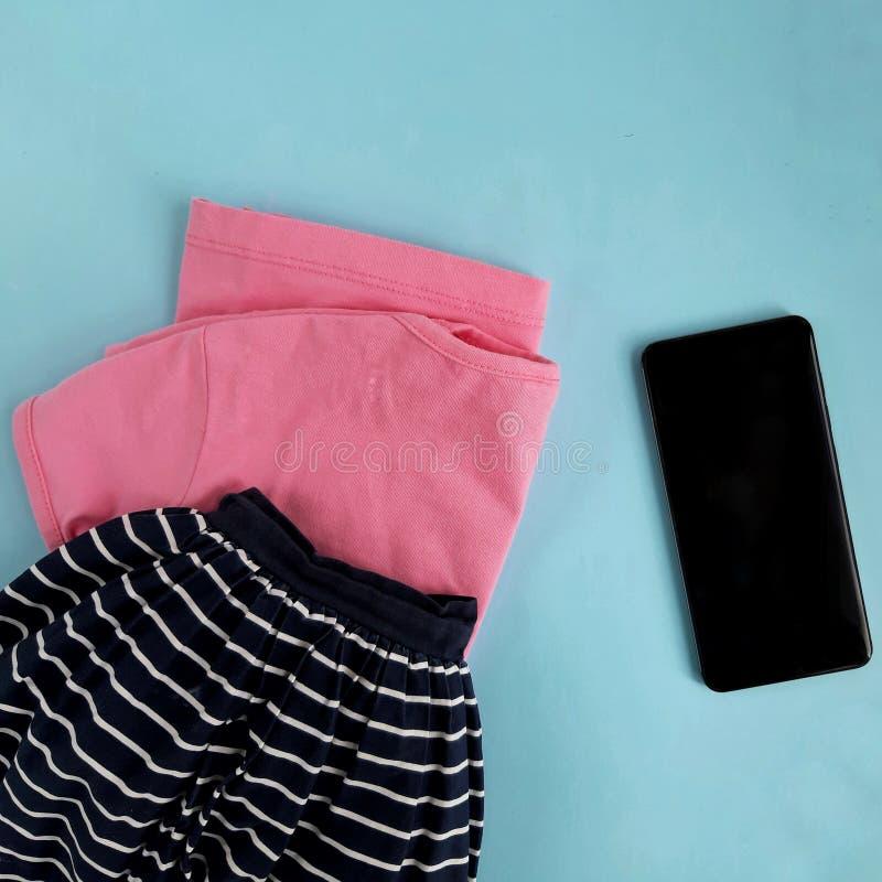 Pink shirt, navy linen skirt, mobile phone on light blue background. Online shopping concept. Pink t-shirt, navy skirt, mobile phone on light blue background stock photos