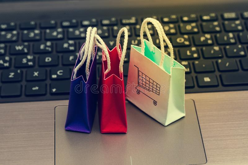 Online shopping concept, Three colorful paper shopping bags on notebook keyboard. E-commerce is the purchase of products and servi. Ces on the internet can stock photos