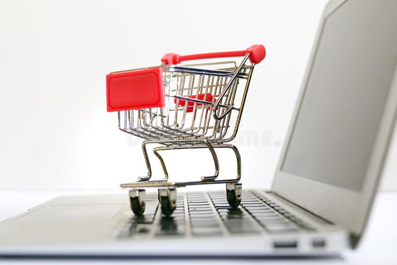 Online shopping concept : trolley cart on a laptop keyboard royalty free stock photo
