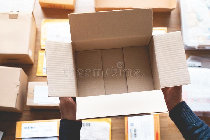 Online shopping concepts with male hand holding brown box on another packet product for shipping to customer stock photo