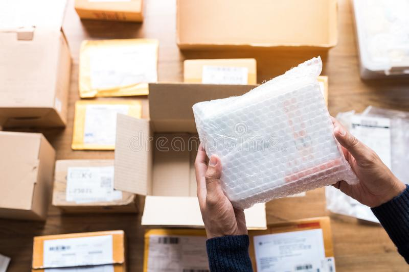 Online shopping concepts with male hand packing some product to brown box on another packet for shipping to customer.Business royalty free stock photos
