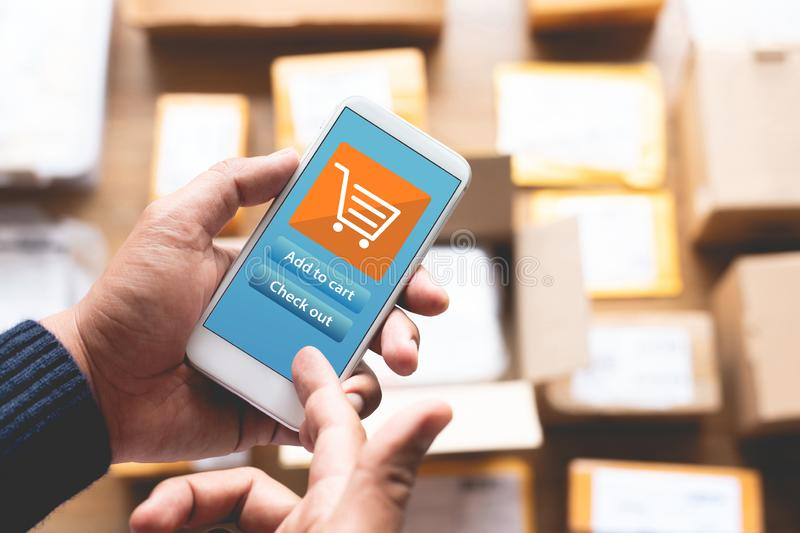 Online shopping concepts with youngman using smartphone for payment his order on a lot of product package box.Ecommerce market. royalty free stock image