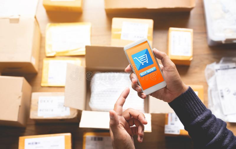Online shopping concepts with youngman using smartphone for payment his order on a lot of product package box royalty free stock photos