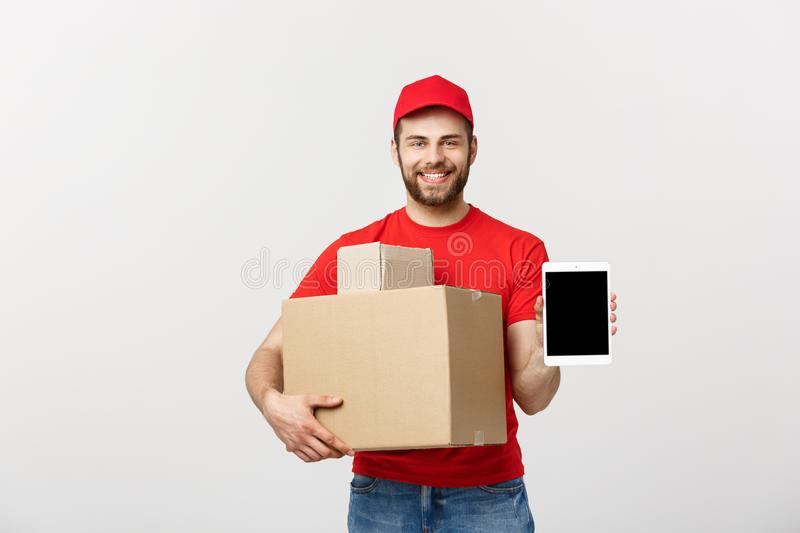 Online shopping, delivery, technology and lifestyle concept - smiling delivery man presenting tablet and holding boxes. In his hand. over white studio stock images