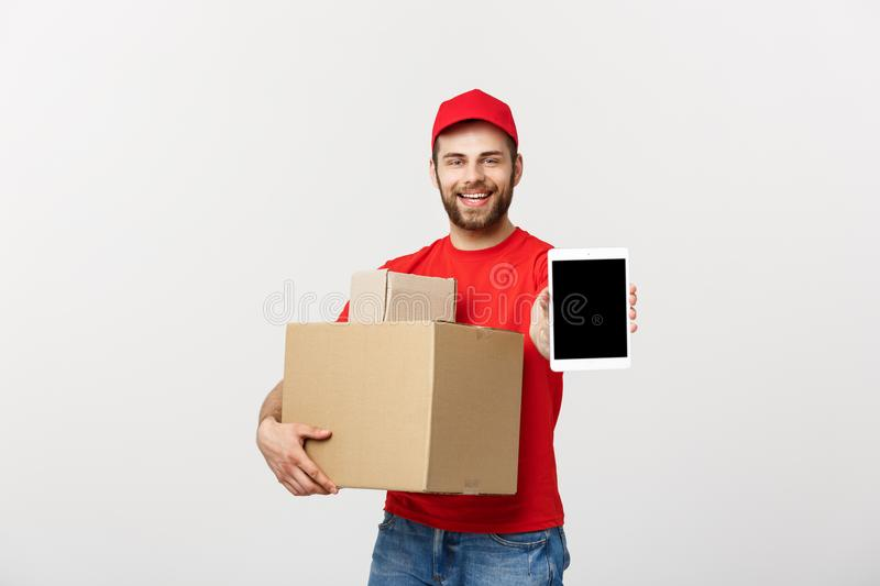 Online shopping, delivery, technology and lifestyle concept - smiling delivery man presenting tablet and holding boxes. In his hand. Isolated over white studio stock image