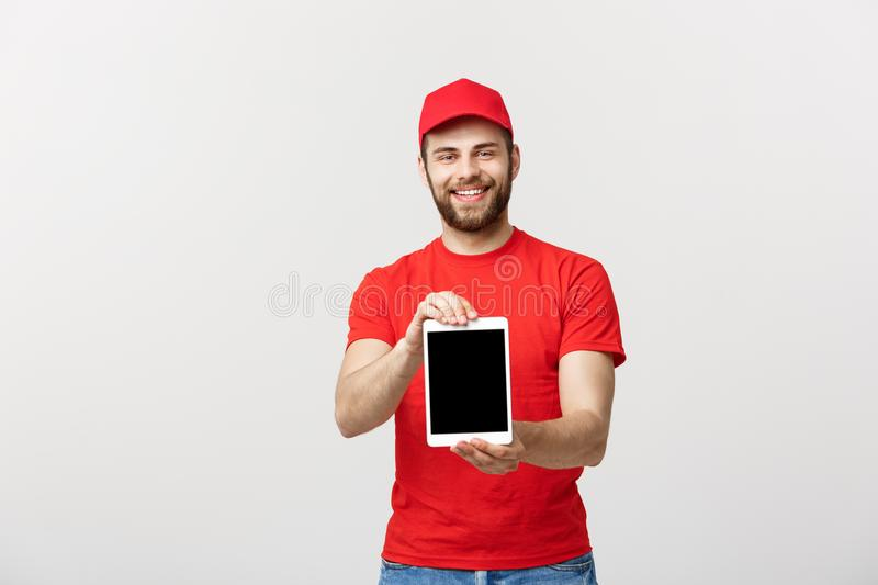 Online shopping, delivery, technology and lifestyle concept - smiling delivery man presenting tablet in his hand showing. Something. Isolated over white studio stock image