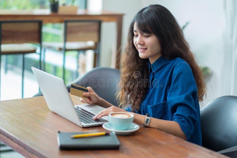 Online-shopping för asiatisk kvinna genom att använda kreditkorten med bärbar datorcomput royaltyfria foton