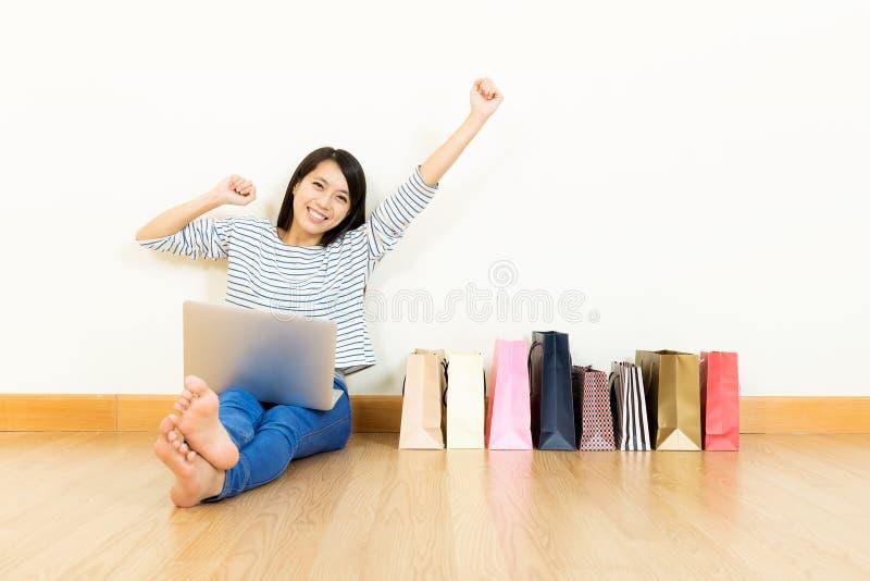 Online-shopping för asiatisk kvinna hemma med den blandade pappers- påsen royaltyfria bilder