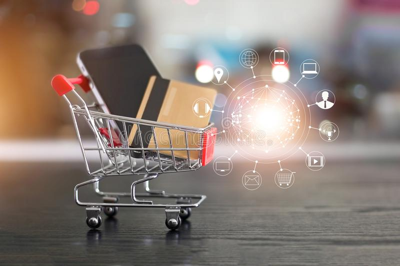 Online shopping. Gold credit card and smartphone in small shopping cart with icon customer network connection. Conceptual. Online shopping. Gold credit card and stock image