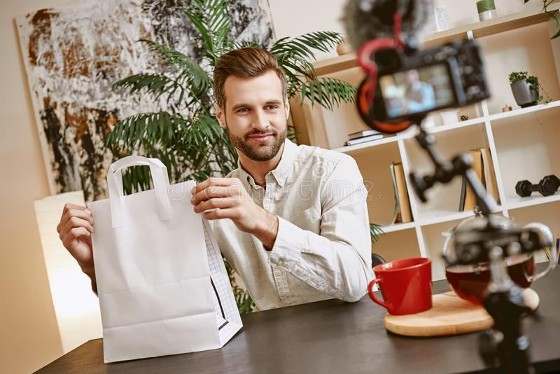 Online shopping. Handsome male blogger holding paper shopping bag and looking at camera while live streaming. Youtube. Fashion blog royalty free stock photography
