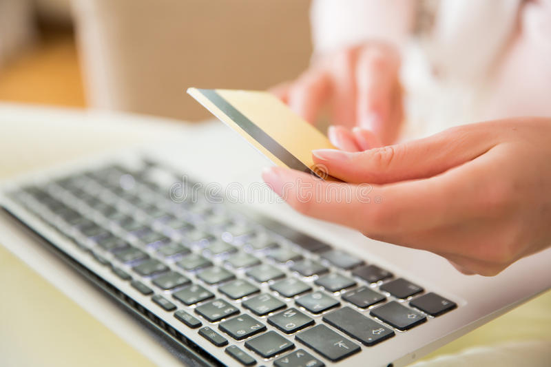 Online shopping. Happy adult woman sitting at home on couch with laptop and credit card. Paying bills and orders. Online shopping and e-commerce concept royalty free stock photo