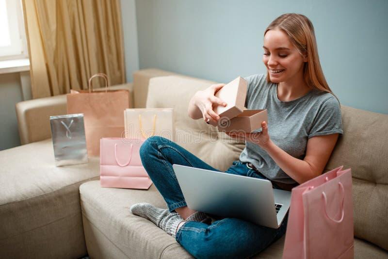 Online-shopping hemma Den unga le shopparen unboxing hennes jordlott och ser in i, beställt och levererat förbi arkivbilder