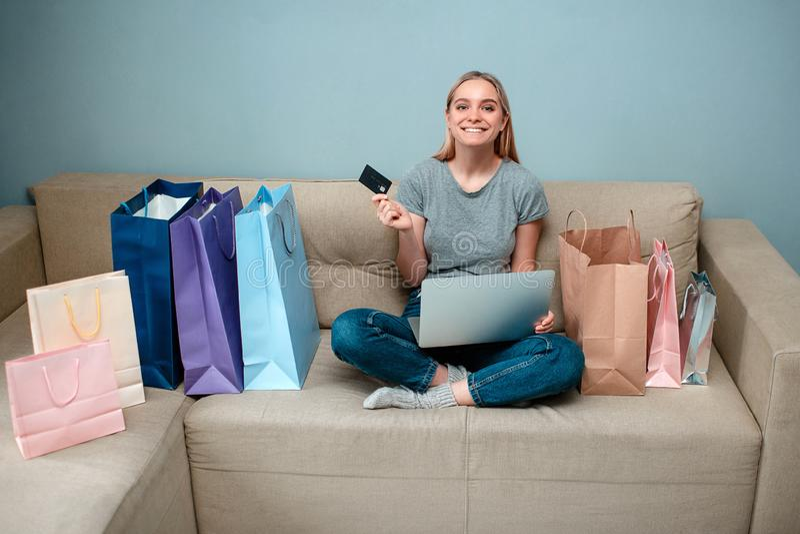 Online-shopping hemma Den unga lyckliga kvinnan med kreditkorten är klar till singeldagen på en soffa nära shoppingpåsar royaltyfria foton