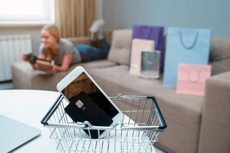 Online shopping at home. Credit card and smartphone on a background of a woman with shopping bags royalty free stock photos