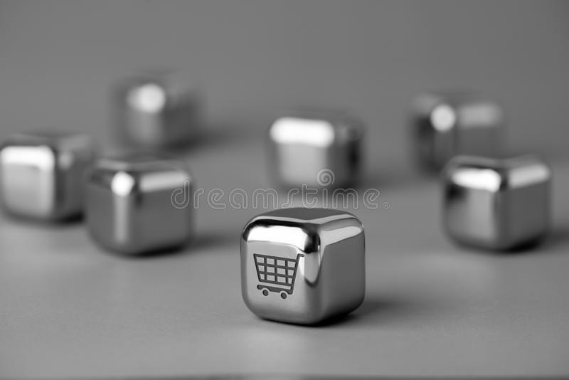 Online shopping icon on metal cube for futuristic & creative style. Lighting in studio stock image
