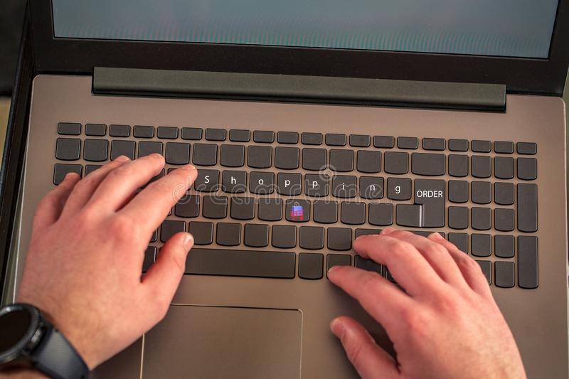 Online shopping-male hands typing on laptop keyboard royalty free stock images