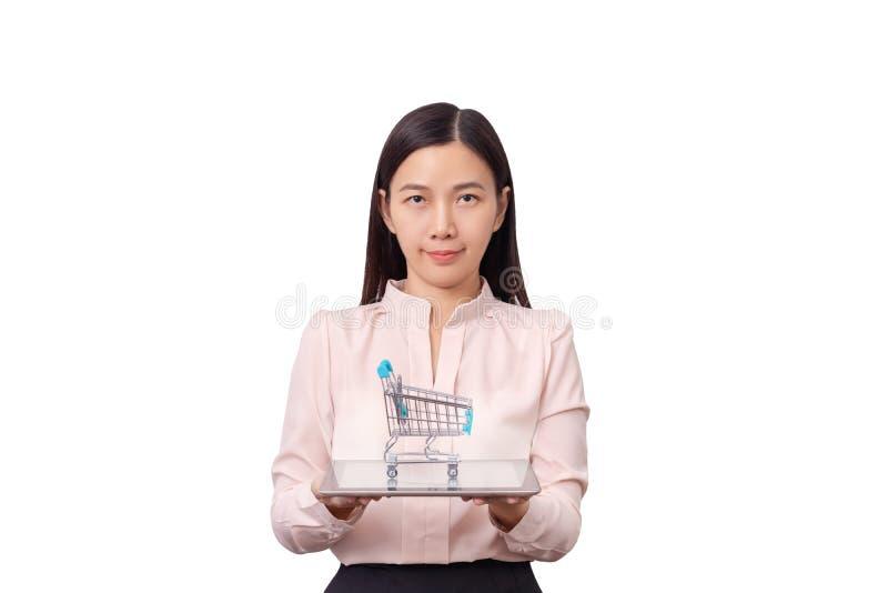 Online-shopping- och E-reklamfilm affärsidé Asiatisk härlig kvinnainnehavminnestavla i hand med den isolerade shoppingvagnen över arkivfoton