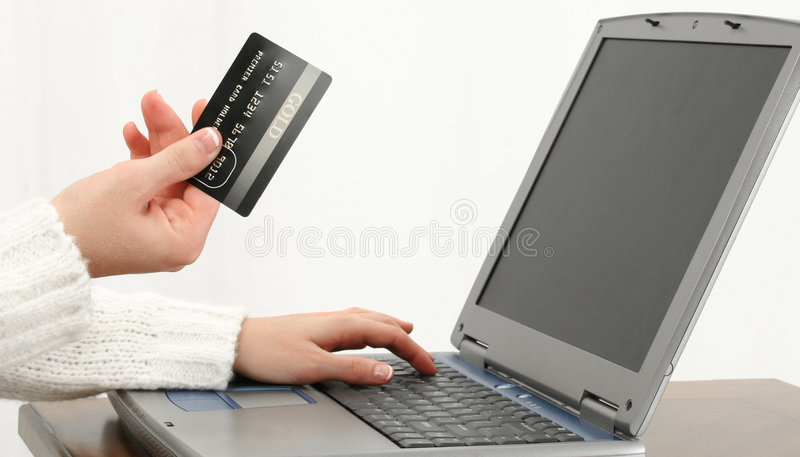 Online Shopping or Paying Bills. Woman's hand at table with Gold Card and Laptop computer. Shopping or Paying Bills. Shot in studio royalty free stock photography